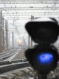 Railway traffic light shows blue signal on railway with blur effect and railway with train as the background Royalty Free Stock Photo