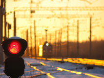 Railway traffic light shows blue signal on railway and railway with freight train as the background Stock Image
