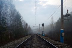 Railway, traffic lights and electric poles in fog. In springtime royalty free stock photos
