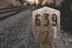 Railway traffic sign next to train tracks with kilometric numbering in concrete marker stock photography