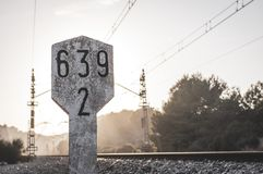 Railway traffic sign next to train tracks with kilometric numbering in concrete marker with sunset raylights. Backlight railway traffic sign next to train tracks royalty free stock images