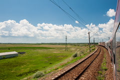 Railway and train go to horizon in green landscape under blue sky with white clouds Stock Images