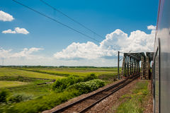 Railway and train go to horizon in green landscape under blue sky with white clouds Royalty Free Stock Photo