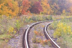 Railway or tramway track in a beautiful autumn park fog. dampness, bright warm autumn colors Royalty Free Stock Photos