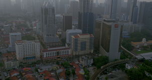 Railway transport and cityscape of Kuala Lumpur, Malaysia. Tilt shot of train moving across the city and Kuala Lumpur panorama with high-rise architecture stock video footage