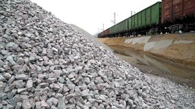 Railway. Transportation of crushed stone by rail. Unloading railway platform. The mountains of crushed granite stock footage