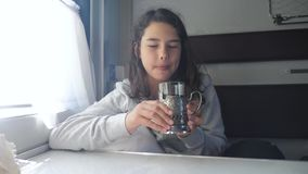 Railway travel concept. little girl at the window drinks tea in a compartment train car. Girl brunette drinks hot tea stock video