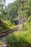 The railway tunnel in a rock on the bank of lake Baikal. Stock Images