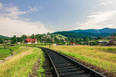 Railway through a village in Carpathians Stock Photography