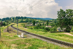 The railway through a village in Carpathians Royalty Free Stock Photo