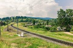 The railway through a village in Carpathians Royalty Free Stock Photo