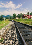 Railway through a village in Carpathians Stock Photography