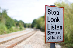 Railway warning sign. Warning sign next to a high speed railway track displaying the words 'Stop Look Listen Beware of trains Royalty Free Stock Photography