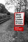 Railway warning sign in black and white with red signpost reading `Stop Look Listen Beware of trains`. With a railway running off into the distance stock images