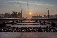Railway whit sunsine. Rail transport is a means of conveyance of passengers and goods, by way of wheeled vehicles running on rail tracks. It is also commonly Royalty Free Stock Photo