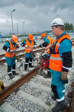 Railway workers repairing rail in rain Royalty Free Stock Photography