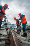 Railway workers repairing rail in rain Royalty Free Stock Images