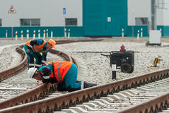 Railway workers repairing rail in rain Royalty Free Stock Photo