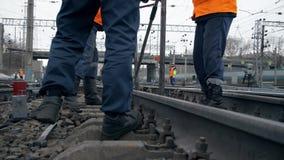 Railwaymans在工作 橙色制服的铁路工作者在铁路线 股票录像