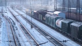 Railways with freight trains on station at winter day. Varifocal lens stock video footage