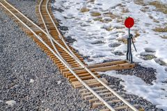 Railways junction on a rocky ground with snow. Close up view of a railroad junction where two rail converge or diverge. A red railroad switch can be seen royalty free stock image