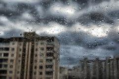 Rain. Drops of rain on a window pane, buildings in background Stock Photo