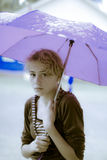 In the rain. Little sad girl stand under umbrella Stock Image