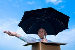 Rain?. Serious man in a cardboard box, with only head and shoulders exposed. Holding an umbrella in one hand, and other hand extended outward palm up.  Blue sky Stock Image
