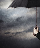 Rain. Human hands holding big black umbrella under the heavy rain Royalty Free Stock Images