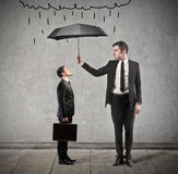 Rain. Businessman protects another men with umbrella Royalty Free Stock Photo