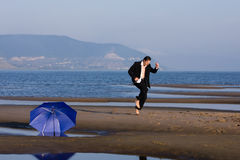 After the rain. Happy businessman dancing on the beach - freedom concept Stock Image