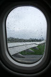 Rain on aeroplane window. Raindrops on window of aeroplane on runway royalty free stock photos