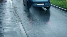 Rain, autumn street background - car rides on the road, puddle a Royalty Free Stock Image
