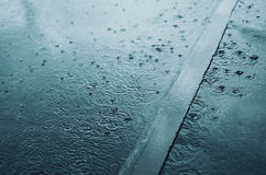 Rain, autumn, weather concept - puddle and splashing water in rainy evening Stock Images
