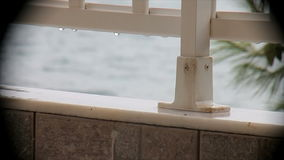 Rain on the balcony overlooking the sea stock footage