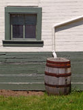 Rain barrel beside nineteenth century building Royalty Free Stock Image