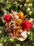 Rain-Beaded Christmas ornaments clustered on outdoor tree Royalty Free Stock Image