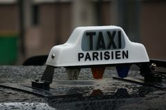 Rain on a black Paris taxi with a white Taxi Parisien sign on top stock photography