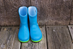 Rain boots. Child's blue rain boots sitting outside on the deck Stock Photography