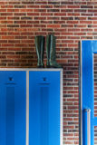 Rain boots. Green rain boots on a blue locker in front of a brick wall royalty free stock images