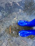 Rain boots. Standing in a puddle with in blue rain boots with bubbles in the rain - April showers stock photography
