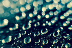 Rain burbles drops and bokeh. Rain drops burbles texture and bokeh background in blue Royalty Free Stock Images