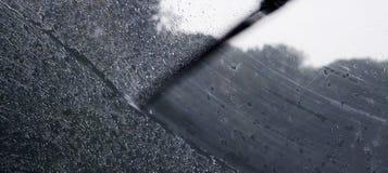 Rain on car window. And windscreen wiper Stock Photos