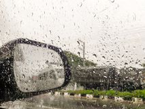 Rain on car windows and reaview mirrors. Royalty Free Stock Image