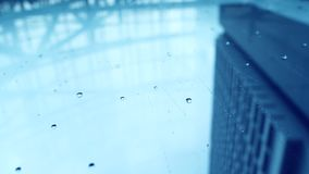 Rain in the city. Bottom view of urban view of rain drops falls on a window during  stormy day overlooking sky and skyscraper in the background stock video footage