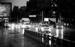 Rain in the city. Rain comes in town, cars are moving in the glare of headlights. Gorod Almaty Stock Photos