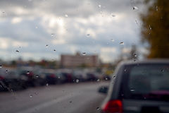 Rain in the city. Rain drops on a car windshield Royalty Free Stock Image