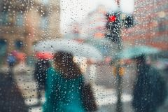 Rain in the city. Gloomy day in the city. People in heavy rain. Selective focus on the raindrops. Prague, Czech Republic Stock Image