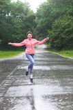 Rain city happy girl jumping in the puddle Royalty Free Stock Photos