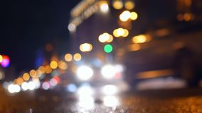 Rain city traffic streets. Defocus night view of holiday lights and city traffic on the streets stock video